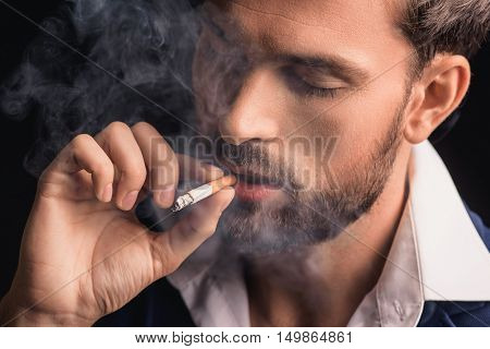 Rich young man is smoking and relaxing. His eyes are closed with pleasure. Isolated on black background