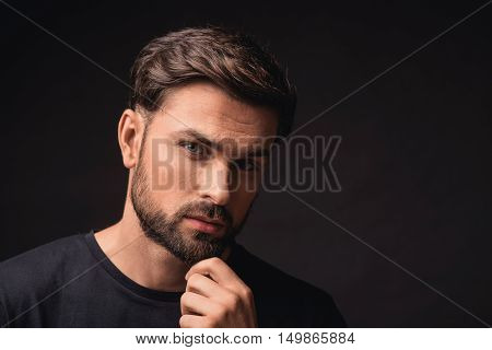 Young man is standing and looking at camera pensively. He is touching his chin. Isolated and copy space in right side