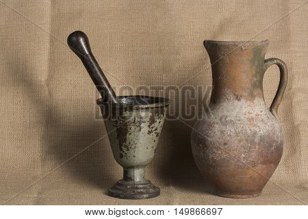 Old vintage rusty mortar and old jar on canvas background.
