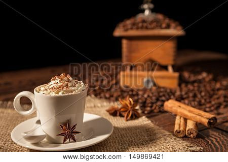 Coffee cup with whipped cream cocoa powder and star anise with coffee grinder on background