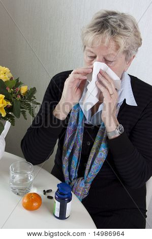 Senior woman has the flue with a huge cold