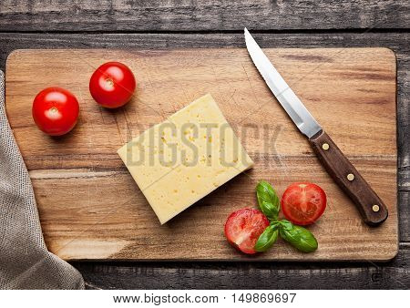 Cheese with tomatoes and basil on wooden cutting board with knife