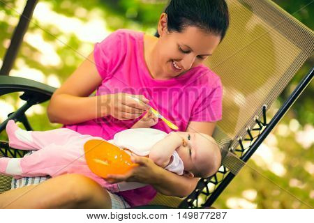 Mother feeding baby girl food to baby