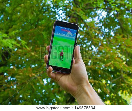 Dnipropetrovsk, Ukraine - July 23, 2016: The male hand holding phone with game Pokemon GO - a free-to-play augmented reality mobile game developed by Niantic for iOS and Android devices.