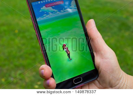 Dnipropetrovsk, Ukraine - July 23, 2016: The female hand holding phone with game Pokemon GO - a free-to-play augmented reality mobile game developed by Niantic for iOS and Android devices.