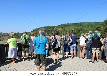 Prague, Czech Republic: 8.9. 2016: Crowd of people standing above the giraffe expoisiton in ZOO Praha (Prague ZOO) tourist nad visitors standing taking photo shot from behind