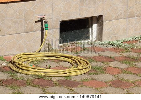 Hose pipe with faucet from wall of house hose laying on pavement with weed with dirty old window to the basement