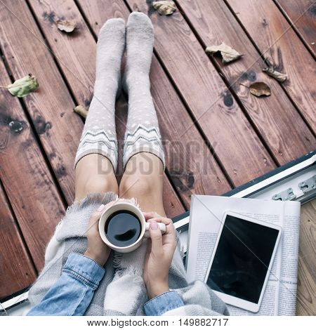 Woman with cup of coffee, tablet computer and paper magazine sitting relaxing home in the window, she's covered in a blanket. Fall leaves on wooden patio deck. Autumn concept.