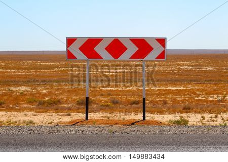 Road sign. Fork. Choice of a way.A pointer to a fork in the desert terrain on the road.