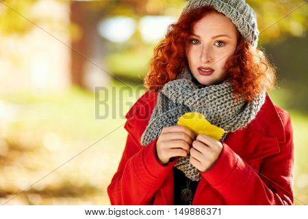 Melancholic ginger girl in autumn with yellow leaf