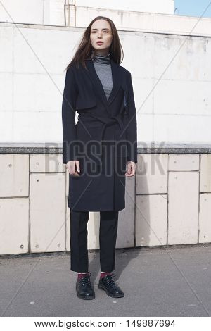 young female fashion model in classic navy trench coat melange blouse and black boots - street style