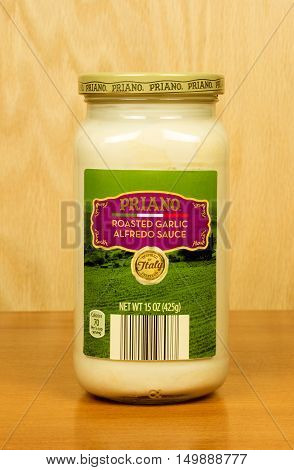 RIVER FALLSWISCONSIN-OCTOBER 022016: A jar of Priano brand garlic alfredo sauce with a wood background.