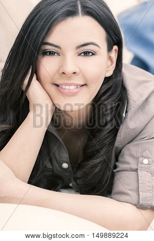 Portrait of a beautiful young Latina Hispanic woman smiling laying down and relaxing at home on a sofa