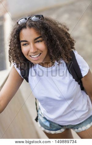 Outdoor portrait of beautiful happy mixed race African American girl teenager female young woman smiling with perfect teeth wearing shorts, t-shirt and back pack
