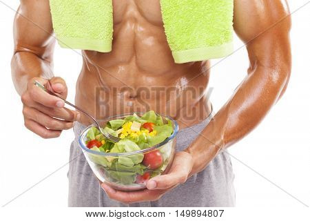 Bodybuilder holding a bowl of fresh salad on white background
