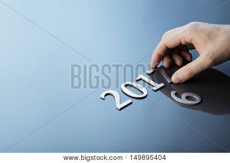 Man making number 2017 using metallic numbers.