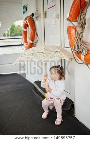 Little girl with umbrella sits on step at door on pleasure boat deck.