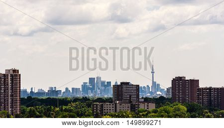 TORONTO CANADA - JULY 10 2016: Older apartment buildings stand among trees in suburban Etobicoke with dense downtown Toronto in the distance.