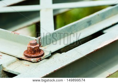 Detail of rusted hexagonal metal screw fastener on corner of painted steel bars and plates.