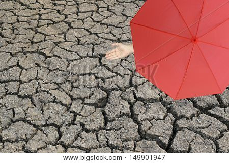 Red umbrella and a hand of man standing on cracked earth and hand protruding outside the radius to determine whether it rains or notconcept of risks in business and nature aridity.