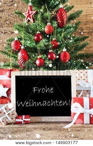 Colorful Christmas Tree With Balls And Snowflakes. Gifts Or Presents In The Front Of Wooden Background. Chalkboard With German Text Frohe Weihnachten Means Merry Christmas