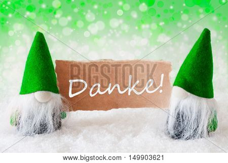 Christmas Greeting Card With Two Green Gnomes. Sparkling Bokeh And Natural Background With Snow. German Text Danke Means Thank You