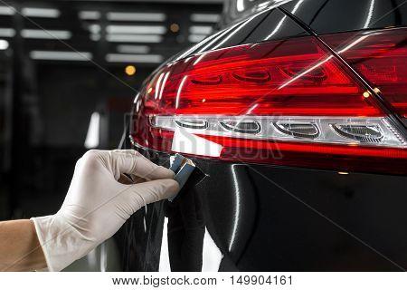 Car detailing series : Closeup of hand coating black car paint