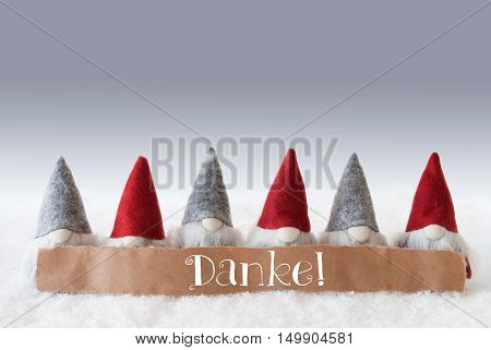 Label With German Text Danke Means Thank You. Christmas Greeting Card With Gnomes. Silver Background With Snow.