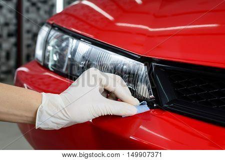 Car detailing series : Closeup of hand coating red car paint