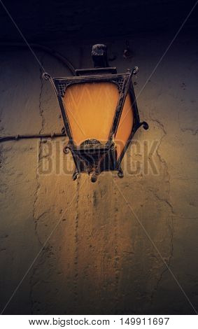 Vintage streetlight on the rustic background at the sunset. Toned image