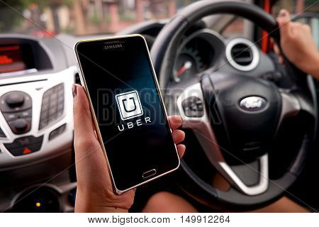CHIANG MAI,THAILAND - SEP 16,2015 : A woman hand holding Uber app showing on Samsung note 3 in the car,Uber is smartphone app-based transportation network.