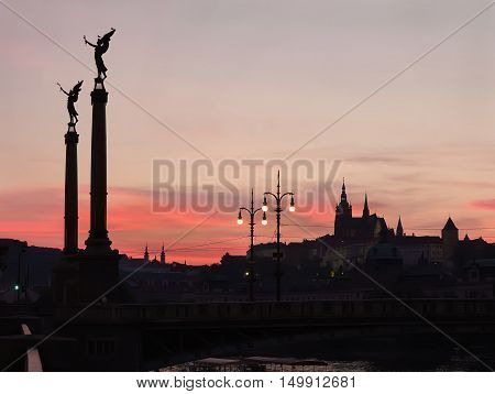 Sunset with silhouettes of Cechuv Bridge and Prague Castle in Prague Czech Republic.