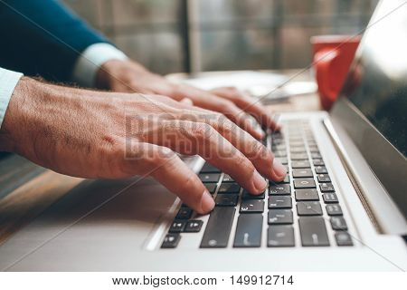Opened laptop and male hands typing. Fingers on the keyboard. Concept of searching information, chating, communication, virtual relationship