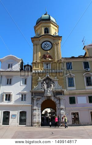 Antique clock tower building situated on main square with old building around it and blue summer sky above