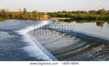 Calming river waterfall full of fresh drinking water with green vegetation and blue sky and few houses in the background