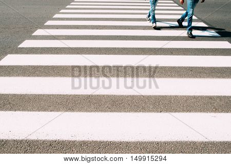 Men running on pedestrian zebra. Two guys in jeans crossing road on walk cross. Busy people, city life, safety walking