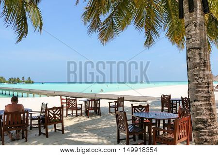 romantic outdoor restaurant table and chairs at the beach on sunset with plam leaves with seaview on a Maldives island