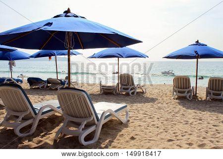 Blue deckchairs under parasol at Adaman Sea in Thailand