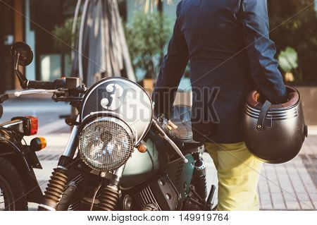 back view of elegant man with helmet standing beside numbered motorcycle