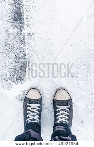 Worn sneakers on grunge pavement as copy space