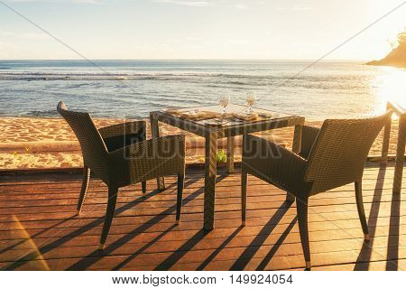 Dining table and two chairs on decking by sea side at evening sun light