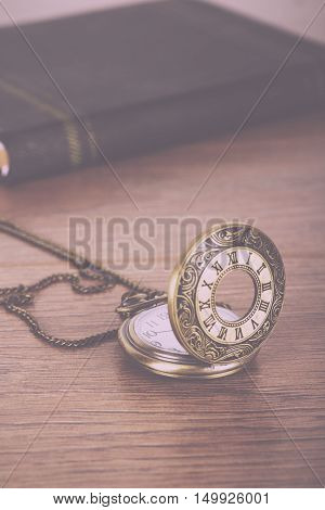 Pocket Watch And Book Against A Rustic Background Vintage Retro Filter.