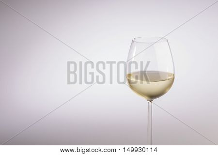 Half filled stylish long stemmed glass of white wine in a close up partial view over a grey background with copy space in a concept of wine wine making and viticulture