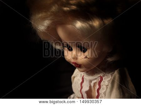Vintage evil spooky doll with cracked surface on the face and glowing eyes