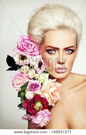 Portrait of young beautiful platinum blonde girl with stylish make-up, prom hairdo and flowers