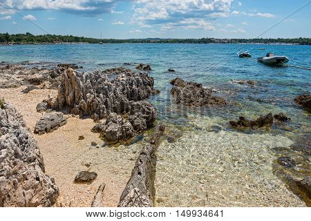 Pathway on the beautiful rocky beach in Istria, Croatian coast. Blue sea, sky and island on horizon.