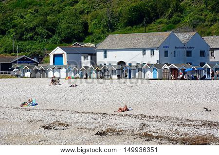 LYME REGIS, UNITED KINGDOM - JULY 18, 2016 - Holidaymakers on the shingle beach with beach huts and the Boat Building Academy to the rear Lyme Regis Dorset England UK Western Europe, July 18, 2016.