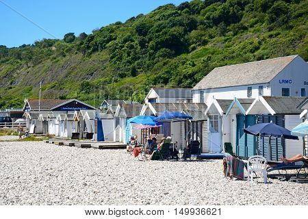 LYME REGIS, UNITED KINGDOM - JULY 18, 2016 - Holidaymakers relaxing outside beach huts on the pebbly beach Lyme Regis Dorset England UK Western Europe, July 18, 2016.