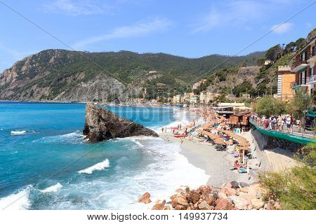 Monterosso, Italy - June 26, 2016: Beach at village Monterosso al Mare and Mediterranean Sea. Monterosso is one of the five villages in Cinque Terre.