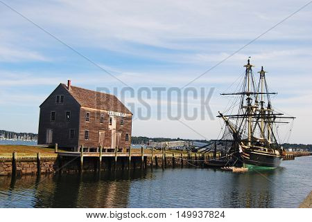 Salem, Massachusetts, United States of America - September 25, 2014. The wharves are among remnants of the shipping industry that once thrived in Salem, MA. View with historic ship, pier and timber building.